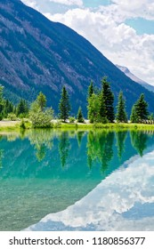 vertical shot of mountains reflected in the teal waters of Field, British Columbia
