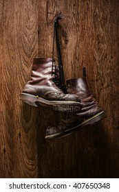 Vertical shot of an old pair of brown boots hanging on a wooden wall