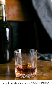 Vertical shot of old-fashioned glass of rum on the vintage wooden chair