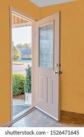 Vertical shot of an open front door leading to the friendly neighborhood.