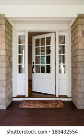 Vertical shot of an open, wooden front door from the exterior of an upscale home with windows.