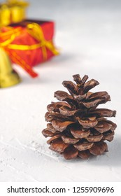 Vertical shot of pine cone like Christmas tree and red and golden decorations in background
