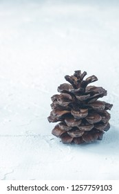 Vertical shot of pine cone like Christmas tree on white textured background with copy space