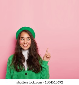 Vertical shot of pleasant looking Asian lady wears green beret and knitted jumper, points fore finger above, has cheerful expression, advertises item on sale, poses over pink wall. Ethicity, promo