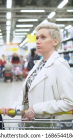 vertical shot. portrait of stylish woman in the supermarket with a grocery cart.