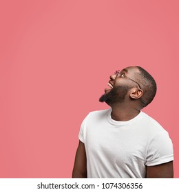 Vertical shot of positive African American male looks happily upwards at blank copy space for your advertising content while poses against pink background. Dark skinned young man in spectacles