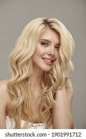 Vertical shot of pretty smiling woman portrait with curly blonde hair and clean skin, studio beauty picture on beige background