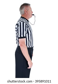 Vertical shot of a professional basketball referee in black and white striped uniform with hands at his sides and blowing a whistle on an isolated white background