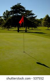 A vertical shot of a red flag on the Green, at a golf course