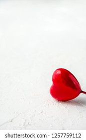 Vertical shot of red glossy heart on white textured background with copy space. Symbol of love and Valentine's day