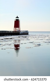Vertical shot of a red lighthouse reflecting in calm water dotted with floating chunks of ice.