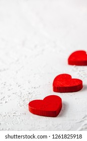 Vertical shot of red wooden hearts in line on white textured background with copy space. Symbol of love and Valentine's day