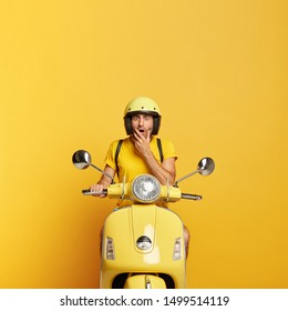 Vertical shot of scared young man stares at camera with frightened face expression, wears yellow protective helmet, t shirt, drives fast motorbike, delivers something for customers, poses indoor