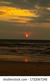 A vertical shot of a sea with the red sun shining behind the clouds in Bình Hưng