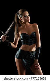 Vertical shot of a sexy young Amazon woman posing with a sword on black background seduction sexuality beauty armored weapon fearless brave tribal culture traditional warrior fighter.