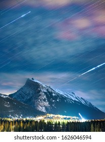 A vertical shot of the snowy mountains under the sky with white linear lights