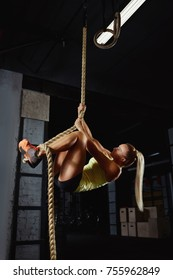 Vertical shot of a sportswoman climbing rope at the gym. Young crossfit female athlete working out at the gym performing rope climbing exercise preparing for competition. Crossfit and fitness