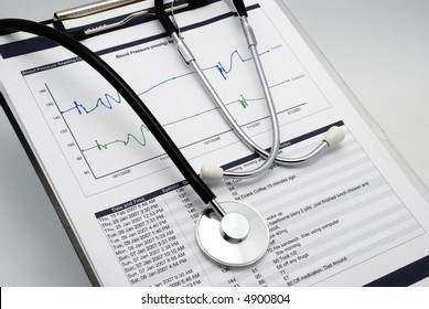 Vertical shot of Stethoscope on clipboard over blood pressure graph printout and table of results