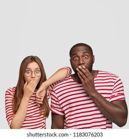 Vertical shot of stupefied dark skinned man with terrified expression, covers mouth with hand, dressed in striped clothes, beautiful woman stands near, react on sudden news, isolated over white wall