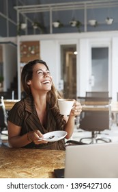 Vertical shot successful carefree girlfriend meet boyfriend lunch drink coffee laughing out loud joyfully raise head up hold cup coffee giggling cheerful near opened laptop visit co-working cafe