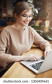 Vertical shot of successful and happy european female student in trendy glasses and casual outfit, smiling broadly while sitting near window in cafe and using laptop to update social page