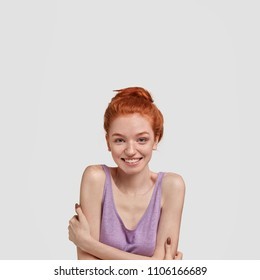 Vertical shot of tender pretty girl has foxy hair combed in knot, keeps hands crossed as trembles from hearing good words from boyfriend, isolated on white background. Cheerful red haired woman