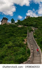 A vertical shot of a tourist climbing up the stairs of the Great Wall of China