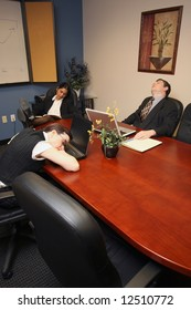 A vertical shot of two businesswomen and a businessman asleep in a conference room.