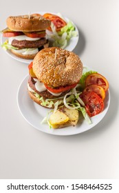 Vertical shot two homemade hamburgers with a juicy meat cutlet, parmesan cheese, green salad, tomatoes and fried potatoes on a light background
