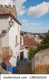 Vertical shot of a typical Portuguese pedestrian road with cobbled stone, orange tree and view of the caste walls from inside Óbidos castle on a sunny day with blue sky and scattered clouds