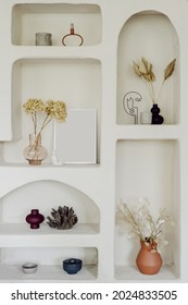 Vertical shot of wall decor, white shelves in apartment interior. Vintage decoration for home indoors, close up of niches in scandinavian room. Natural decor with dry plants in vase.