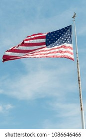 vertical shot of a waving American flag on a pylon with an eagle on top against blue sky