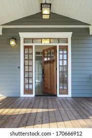 Vertical shot of wooden front door  of an upscale home with windows/Exterior shot of an open Wooden Front Door