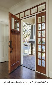 Vertical shot of wooden front door from the interior of an upscale home with windows/Interior shot of Wooden Front Door