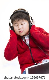 Vertical shot of a young Asian boy in red enjoying his moment  listening to music with a headphone isolated on white.