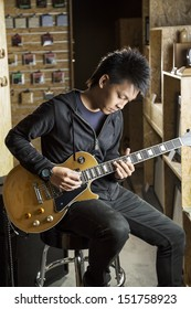 A vertical shot of a young asian man playing electric guitar.