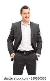 Vertical shot of a young confident businessman in a black suit posing and looking at the camera isolated on white background