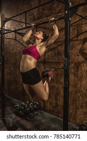 Vertical shot of a young sportswoman doing butterfly kipping pull-ups at the gym functional crossfit training workout exercising back arms biceps muscles toned healthy lifestyle strengthening effort