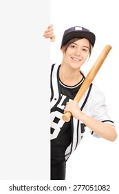 Vertical shot of a young woman in a baseball jersey posing behind a blank billboard with a baseball bat in her hand isolated on white background