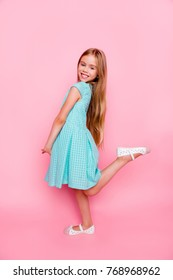Vertical side view full-size, full-length portrait of cute lovely gentle tender little girl wearing light blue dress, she is smiling and  raising up a leg, isolated on pink background