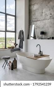 Vertikales und seitliches Foto des modernen Hauses mit zeitgenössischem Interieur in weißem Badezimmer mit komfortabler Badewanne, hausgemachtes Dekor und frische Handtücher am Holztisch