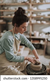 Vertical side view portrait of beautiful craftswoman making clay bowl in pottery workshop