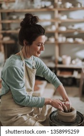 Vertical side view portrait of beautiful craftswoman making clay bowl in pottery workshop. She smiling