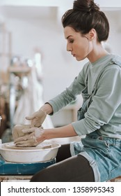 Vertical side view portrait of serious focused craftswoman creating clay pot on pottery wheel