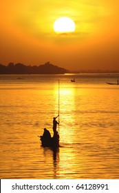 Vertical silhouette of African fisherman in canoe at sunset