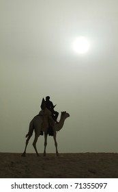 A vertical silhouette of a Tuareg rider and camel with bright sun