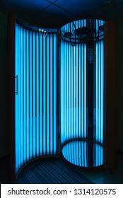 vertical Solarium with glowing blue light ultraviolet lamps for tanning and skin care
