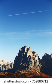 Vertical solo view of Sassolungo (Langkofel) peak in the Dolomites with deep blue sky and an airplane trail above