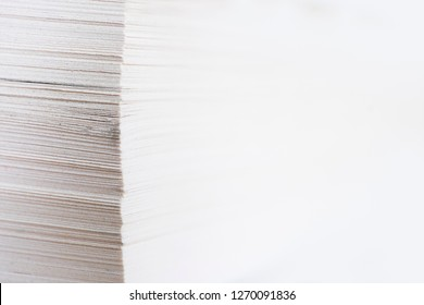Vertical stack of papers with with shallow depth of field. Right side is completely white