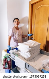 Vertical stock photo of a hotel cleaner entering a room with a cleaning trolley and clean towels